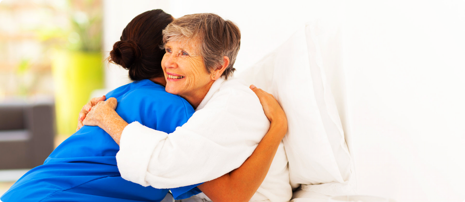 A nurse and an elderly hugging each other